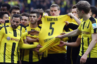 DORTMUND, GERMANY - APRIL 15: Players of Dortmund hold the jersey of their injured team mate Marc Bartra after winning the Bundesliga match between Borussia Dortmund and Eintracht Frankfurt at Signal Iduna Park on April 15, 2017 in Dortmund, Germany.