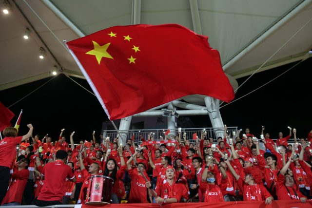 "A Chinese fan waves the national flag during a world cup qualifier at Mong Kok stadium in Hong Kong on November 17, 2015. Hong Kong fans booed the anthem they share with China on Tuesday while some turned their backs and held up ""boo"" signs in a show of defiance before a crunch World Cup football qualifier with their mainland rivals."
