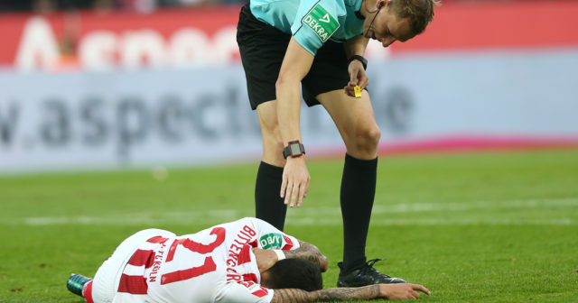 COLOGNE, GERMANY - SEPTEMBER 20: Leonardo Bittencourt of Koeln lies on the pitch and is checked on by referee Martin Petersen during the Bundesliga match between 1. FC Koeln and Eintracht Frankfurt at RheinEnergieStadion on September 20, 2017 in Cologne, Germany. (Photo by Christof Koepsel/Bongarts/Getty Images)